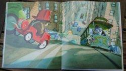 Straßenszene aus dem Bilderbuch: Oscar saust als Feuerwehrmann im kleinen roten Auto die Hügelstraßen hinunter